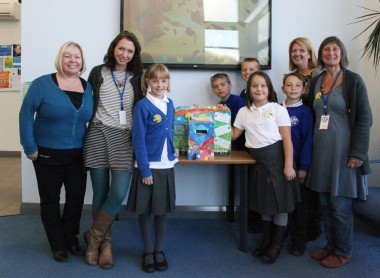 The story collection box at Praze Surgery. From left to right- a representative from Praze Surgery, Sarah from Storylines, Logan, Marnie, Roxxi, Max, Jackie Spoors- class teacher of Crenver class and Ali from Storylines. Credit- Taken by year 6 pupil Daisy